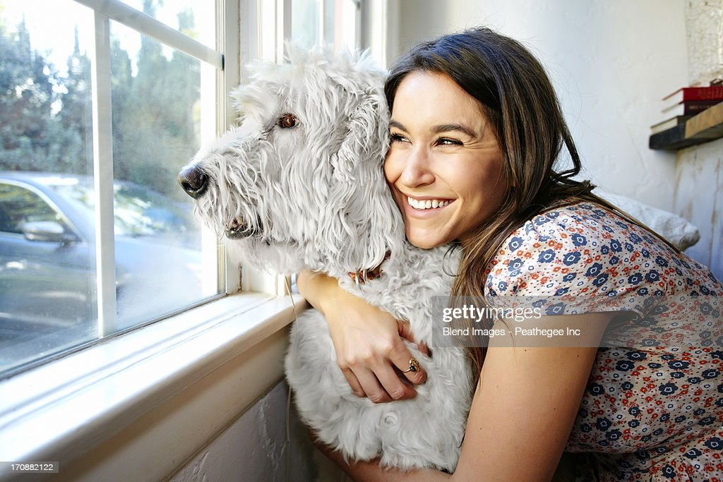 Caucasian woman hugging dog at window : Stock Photo