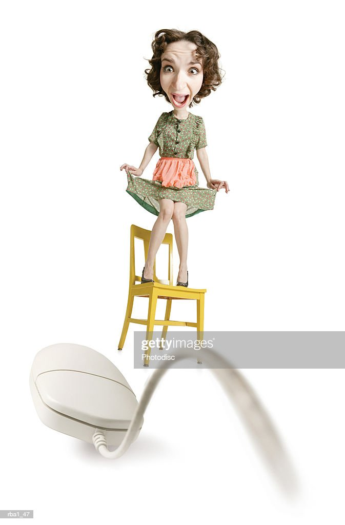 caucasian woman in 50s housewife clothes stands on a chair terrified by a computer mouse : Stockfoto