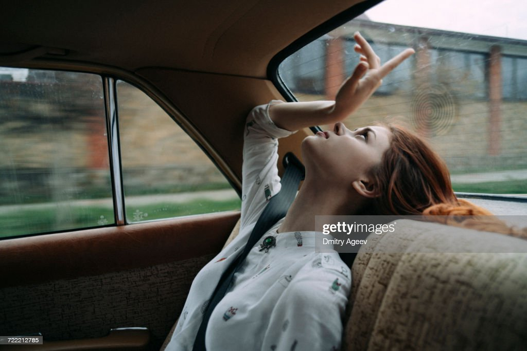 Caucasian woman in back seat of car looking up : Stock Photo