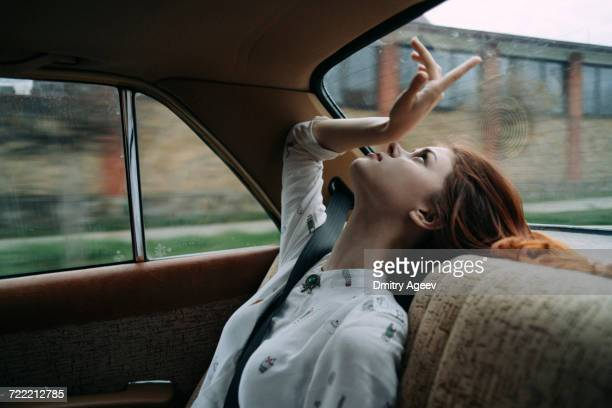 caucasian woman in back seat of car looking up - boredom stock pictures, royalty-free photos & images