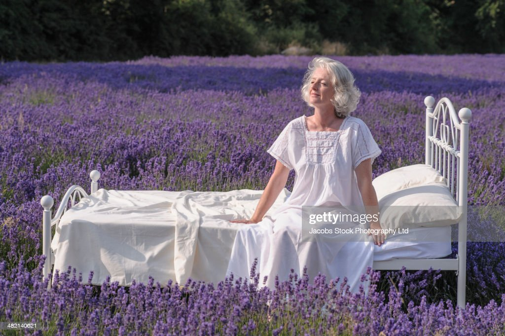 Caucasian woman in bed in lavender field : Stock Photo