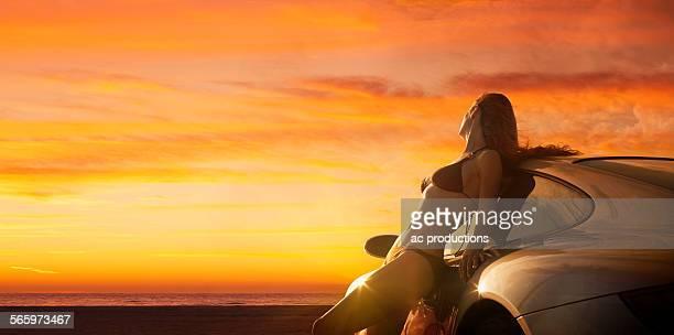 Caucasian woman in bikini leaning on sports car at sunset