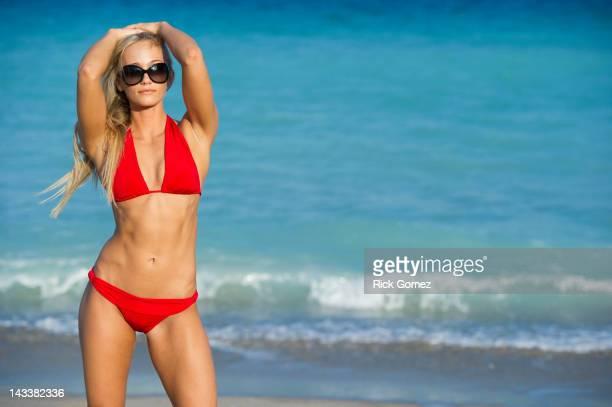 Caucasian woman in bikini standing on beach
