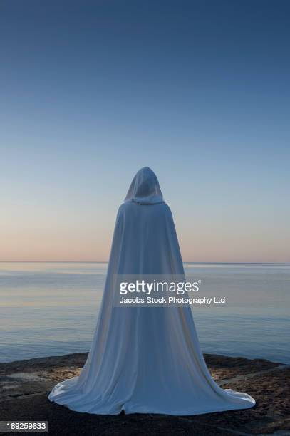 Caucasian woman in cape overlooking ocean