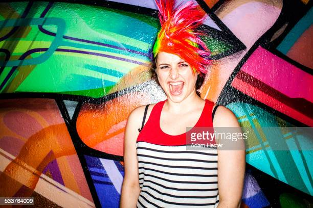 Caucasian woman in colorful wig laughing near graffiti wall