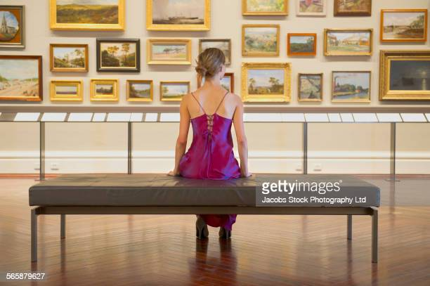 caucasian woman in evening gown admiring art in museum - museo fotografías e imágenes de stock