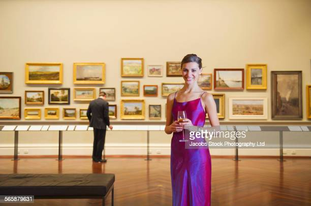 Caucasian woman in evening gown smiling in art museum