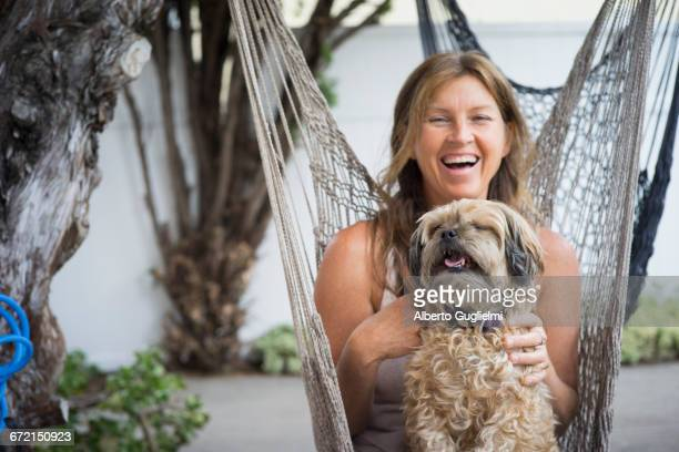 Caucasian woman in hammock holding dog and laughing