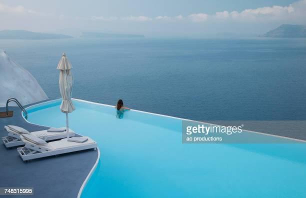 caucasian woman in infinity pool admiring scenic view of ocean - luxe stockfoto's en -beelden