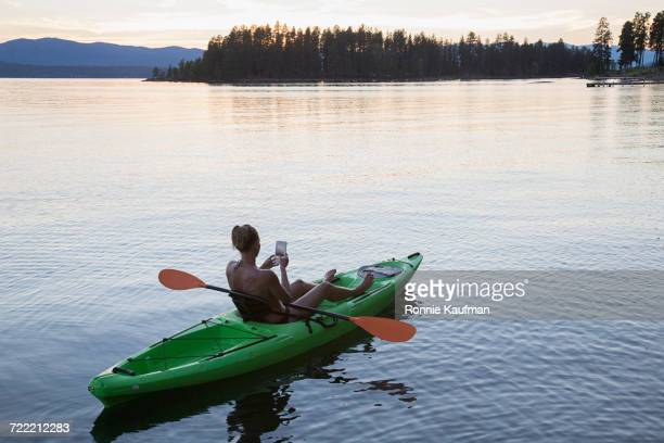 Caucasian woman in kayak on river texting on cell phone