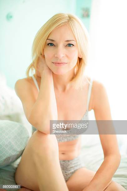 Caucasian woman in lingerie sitting on bed