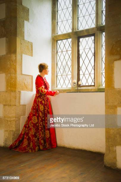 Caucasian woman in medieval costume looking out castle window