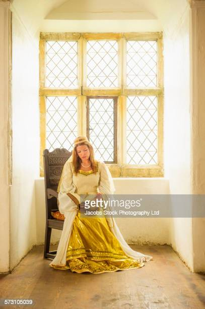 Caucasian woman in medieval costume sitting at window