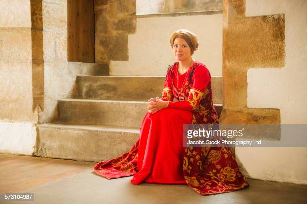 Caucasian woman in medieval costume sitting in castle
