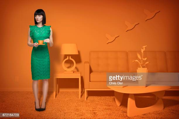 caucasian woman in orange old-fashioned livingroom drinking coffee - green dress stock pictures, royalty-free photos & images