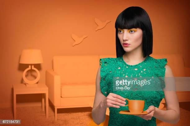 Caucasian woman in orange old-fashioned livingroom drinking coffee