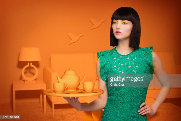 Caucasian woman in orange old-fashioned livingroom holding tea service