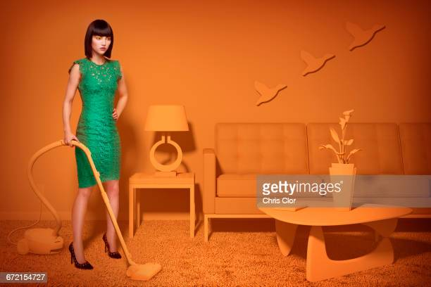 Caucasian woman in orange old-fashioned livingroom vacuuming carpet