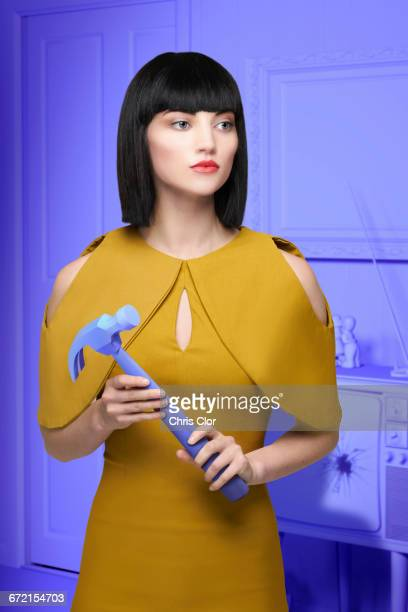 Caucasian woman in purple old-fashioned livingroom holding hammer