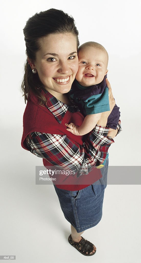 caucasian woman in red vest and denim skirt with big smile holds laughing infant : Foto de stock