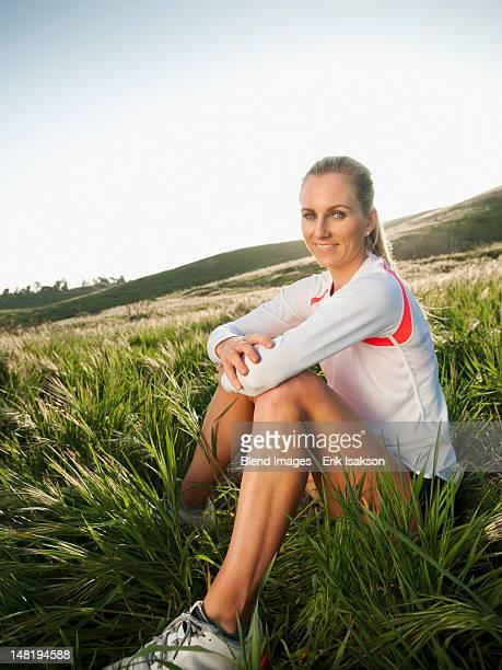 Caucasian woman in sportswear sitting in field