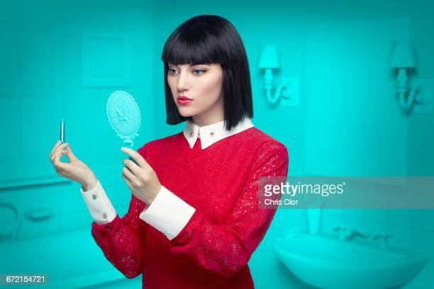 Caucasian woman in teal old-fashioned bathroom applying lipstick