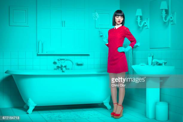 Caucasian woman in teal old-fashioned bathroom holding cleaning brush