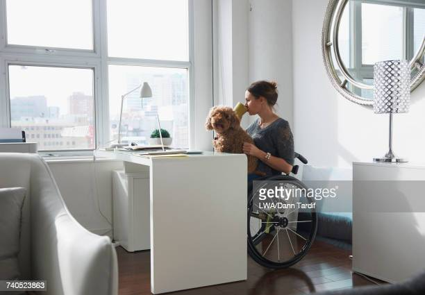 Caucasian woman in wheelchair drinking coffee with dog in lap