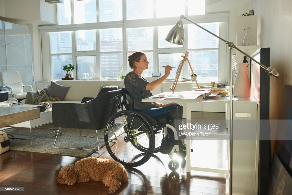 Caucasian woman in wheelchair painting on easel : Stock Photo
