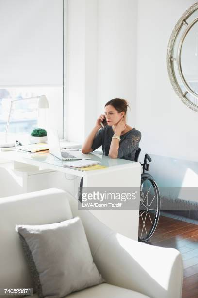 Caucasian woman in wheelchair using laptop and talking on cell phone