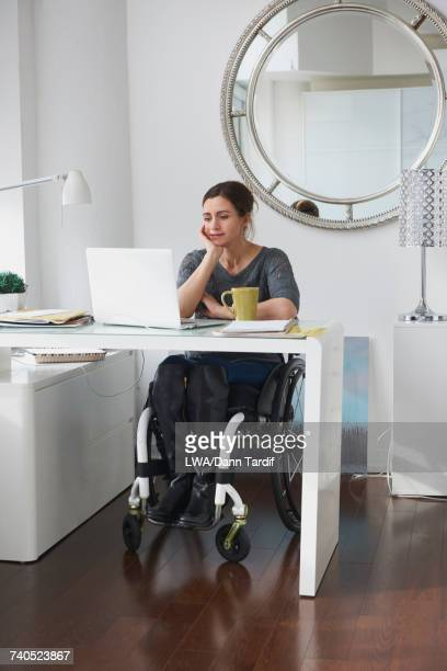 Caucasian woman in wheelchair using laptop in home office