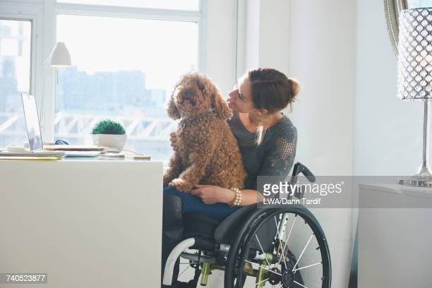 Caucasian woman in wheelchair with dog in lap