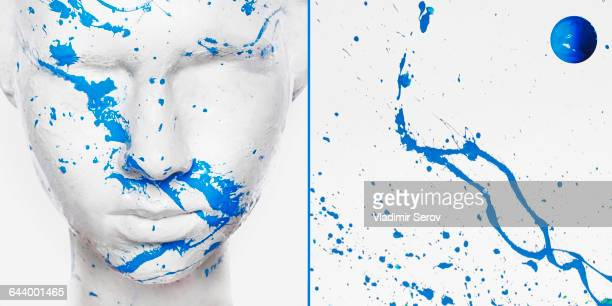 Caucasian woman in white makeup splashed with blue paint