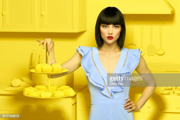 Caucasian woman in yellow old-fashioned kitchen holding dessert tray