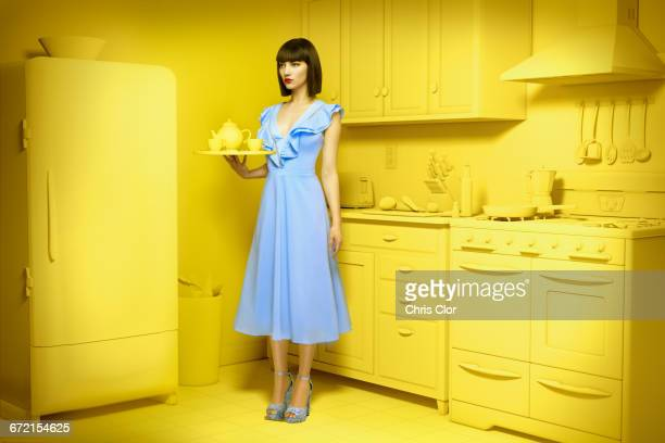 Caucasian woman in yellow old-fashioned kitchen holding mixing bowl