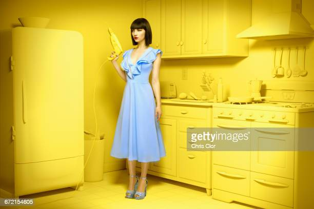 Caucasian woman in yellow old-fashioned kitchen holding power drill