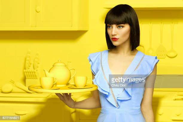 Caucasian woman in yellow old-fashioned kitchen holding tea service
