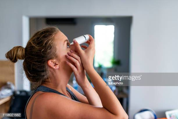 mulher caucasiano que introduz eye-drops - gota condição médica - fotografias e filmes do acervo