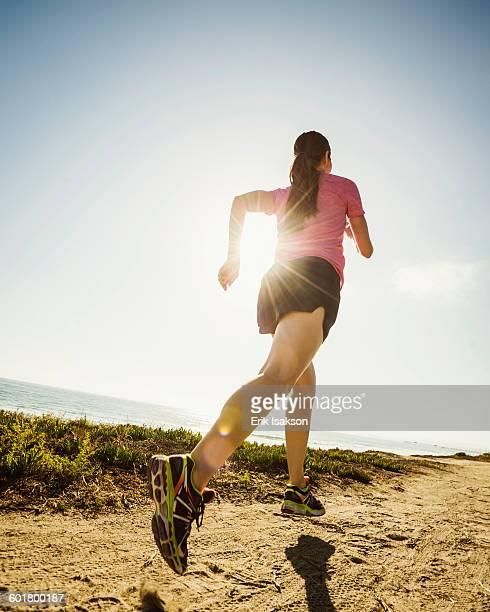 Caucasian woman jogging on dirt path