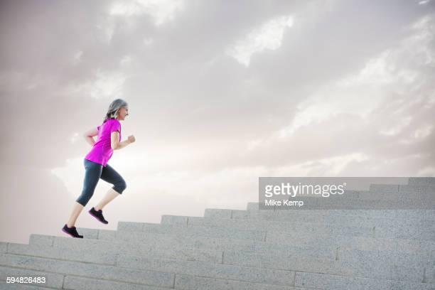Caucasian woman jogging on steps
