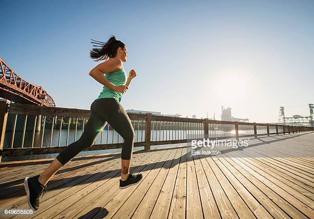 caucasian woman jogging on urban waterfront - extra long stock pictures, royalty-free photos & images