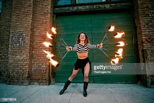 caucasian woman juggling fire on city sidewalk - circus stock photos and pictures