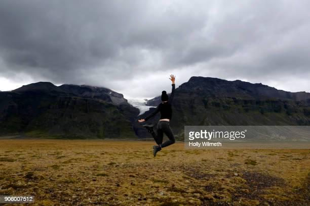 Caucasian woman jumping for joy in field