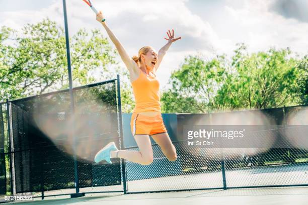 caucasian woman jumping for joy on tennis court - ラケット ストックフォトと画像