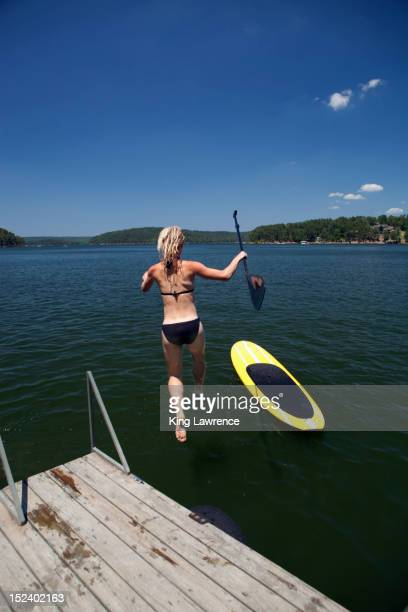 caucasian woman jumping in lake next to paddleboard - tennessee v arkansas stock pictures, royalty-free photos & images