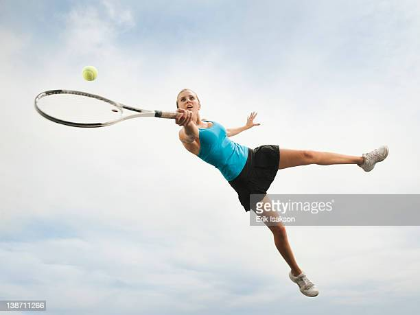 caucasian woman jumping in mid-air playing tennis - human arm fotografías e imágenes de stock
