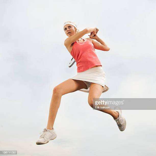 Caucasian woman jumping in mid-air playing tennis