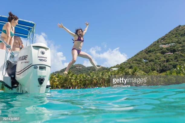 Caucasian woman jumping off boat in tropical ocean