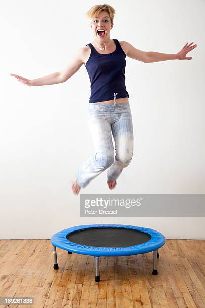Caucasian woman jumping on indoor trampoline
