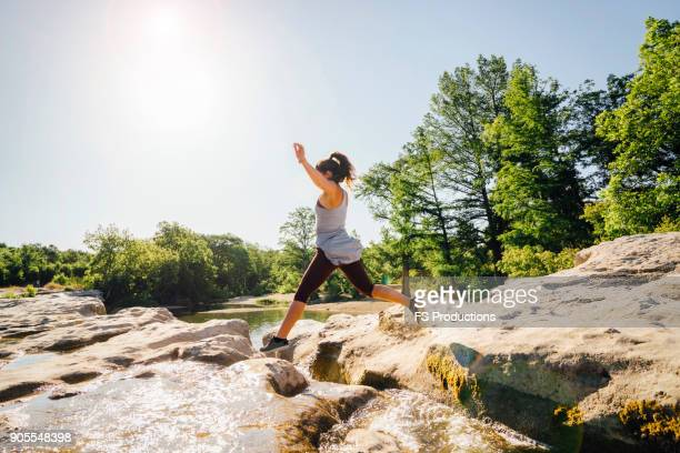 caucasian woman jumping on rocks near river - austin texas stock photos and pictures